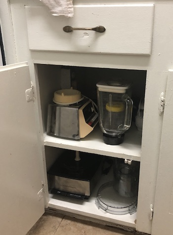 A kitchen cupboard with a food processor and blender