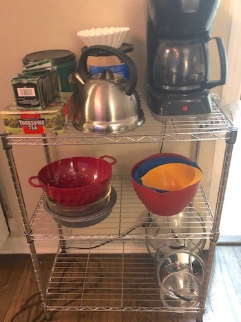A shelf with mixing bowls, a coffee maker, coffee, tea, and measuring cup