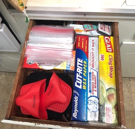 A kitchen drawer with cling wrap, aluminum foil, wax paper, ziploc bags, silicon mitts, pot holders, and various fast food condiments