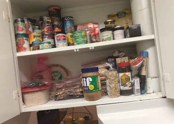 A kitchen cupboard with dried goods, canned goods, nuts, seeds, dried fruits
