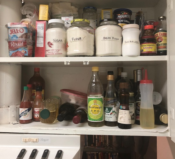 A kitchen cupboard with oils, vinegars, hot sauces, and baking supplies