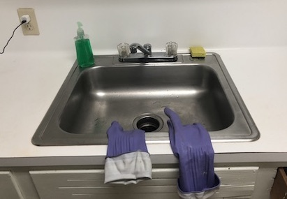 A kitchen sink with dish soap, a sponge, and rubber gloves